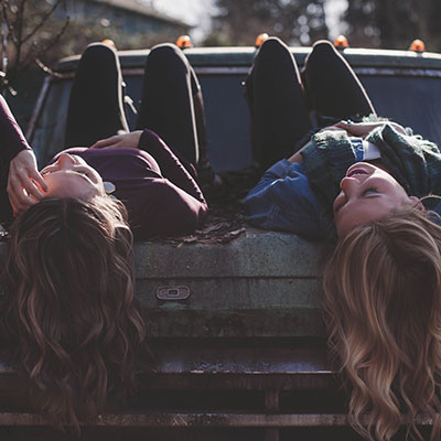 Teen girls laying on truck